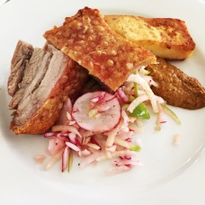 Crispy Pork Belly served with a radish and green apple slaw, roasted capsicum pesto, and accompanied by polenta chips.